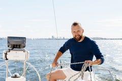 Stilig skäggig grabb som spolar ett rep på en yacht Royaltyfri Bild