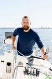 Stilig skäggig grabb som spolar ett rep på en yacht Arkivbilder