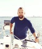 Stilig skäggig grabb som spolar ett rep på en yacht Resa vaca Arkivbild