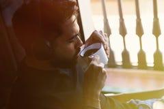 Stilig skäggig man i hörlurar som lyssnar till musik och den enkoing koppen kaffe hemma Tillfällig koppla av och vilotid Arkivbilder