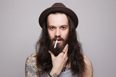 stilig skäggig man i hatten som röker en cigarett Royaltyfri Bild