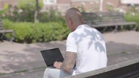 Stilig skallig mitt - östlig affärsman som arbetar med bärbara datorn som sitter på bänken i gatan Frilans- begrepp man lager videofilmer