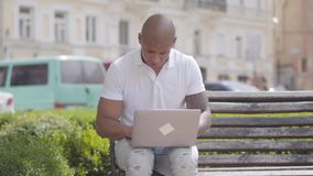 Stilig skallig mitt för stående - östlig affärsman som arbetar med bärbara datorn som sitter på bänken i gatan frilans arkivfilmer