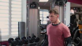 Stilig sportig biceps för manutbildningshantel i idrottshallen arkivfilmer