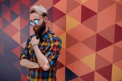 Stilig st?ende av en ung hipsterman som poserar n?ra multicolorebakgrund, ikl?dd f?rgrik skjorta arkivbilder