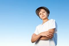 Stilig stående yttersida för tonårs- pojke mot en blå himmel Arkivfoton