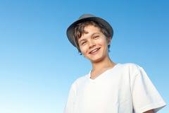 Stilig stående yttersida för tonårs- pojke mot en blå himmel Royaltyfri Bild