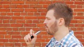 Stilig stilfull man som röker vap mot en tegelstenvägg och ser in i kameran, långsam-mo, innegrej arkivfilmer