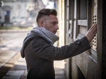 Stilig stilfull ung man som ringer ringklockan på byggnad arkivfoto