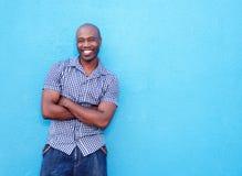 Stilig svart man som ler med korsade armar royaltyfri bild