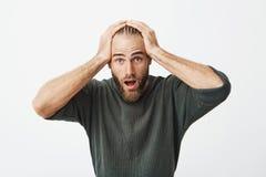 Stilig svensk man med moderiktiga frisyr- och skägginnehavhänder på head chockat vid nyheterna den hans favorit- musik arkivfoto
