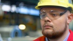 Stilig tekniker som går i en fabrik industriell bakgrund lager videofilmer
