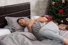 Stilig trött man i pajama som bara sover och kramar en kudde royaltyfri bild