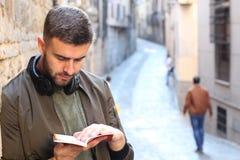 Stilig turist som konsulterar en handbok under ett lopp runt om Europa arkivfoton
