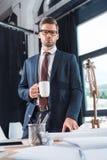 stilig ung affärsman i glasögon som rymmer koppen kaffe och att se fotografering för bildbyråer