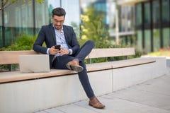 Stilig ung affärsman med smsande sms för bärbar dator på hans smartp royaltyfria bilder