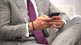 Stilig ung affärsman som använder smartphonen som ler det lyckliga bärande dräktomslaget använda för affärsmansmartphone Mansms arkivfilmer