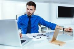 Stilig ung affärsman som arbetar med bärbara datorn i kontoret royaltyfri fotografi