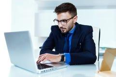 Stilig ung affärsman som arbetar med bärbara datorn i kontoret royaltyfria bilder