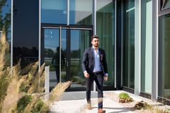 Stilig ung affärsman som går ut ur en kontorsbyggnad royaltyfri foto
