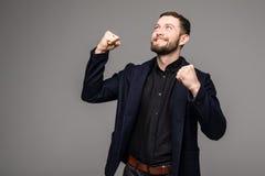 Stilig ung affärsman som gör en gest och ler Arkivbild