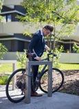 Stilig ung affärsman som parkerar hans cykel på arbete royaltyfri fotografi