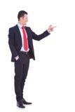 Stilig ung affärsman som pekar till hans sida royaltyfri bild