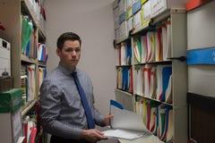 Stilig ung affärsman som söker mappar Royaltyfri Bild