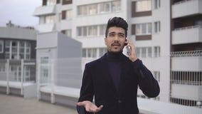Stilig ung affärsman som talar på smartphonen och går bort le det lyckliga bärande dräktomslaget utomhus lager videofilmer
