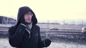 Stilig ung affärsman som talar på smartphonen som utomhus ler det lyckliga bärande dräktomslaget lager videofilmer