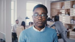 Stilig ung afrikansk amerikanaffärsman i exponeringsglas som ler på kameran Stilfull manlig kontorsarbetare för Hipster som poser arkivfilmer