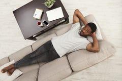 Stilig ung afrikansk amerikanman som hemma kopplar av på soffan royaltyfri fotografi