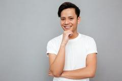 Stilig ung asiatisk man som står över grå bakgrund Arkivbilder