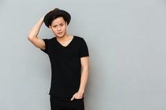 Stilig ung asiatisk man som står över grå bakgrund Royaltyfria Foton
