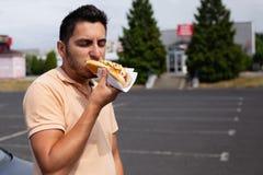 Stilig ung brunettman som äter varmkorven arkivfoto