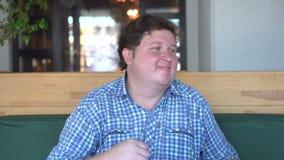 Stilig ung fet man i skjortadans i kafé eller restaurang Fett grabbdanssammanträde arkivfilmer