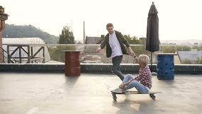 Stilig ung grabb med hans flicka som har gyckel på skateboarderna på taket av industribyggnad gyckel som har folk två lager videofilmer