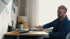 Stilig ung hem- freelancer med exponeringsglas och gult hår som hemma arbetar, genom att använda en bärbar dator Medan få dåliga  lager videofilmer