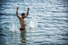 Stilig ung kroppsbyggare i havet, plaskande vatten upp Arkivbild