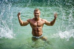 Stilig ung kroppsbyggare i havet, plaskande vatten upp Royaltyfri Bild