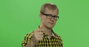 Stilig ung man i den gula skjortan som gör göra kommande gest Tv? i en: 1 lager videofilmer