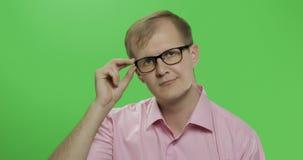 Stilig ung man i den rosa skjortan som vänder hans huvud och ser i kameran stock video