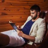 Stilig ung man i den vita dräkten som kopplar av på den lyxiga soffan med dagboken royaltyfri bild