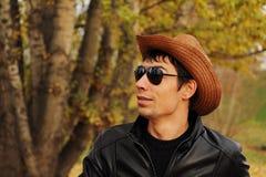 Stilig ung man i exponeringsglas och en hatt Arkivfoto