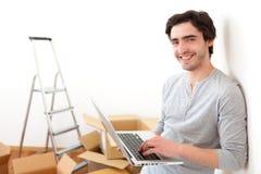 Stilig ung man i hans nya plana användande bärbar dator Arkivbild
