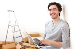 Stilig ung man i hans nya plana användande bärbar dator Royaltyfria Bilder