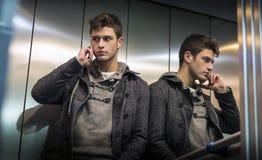 Stilig ung man i hissen (elevator) som använder mobiltelefonen Arkivbilder