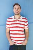 Stilig ung man i randig skjorta som skrattar mot den blåa väggen Arkivbilder
