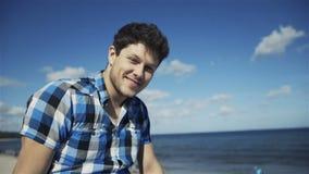 Stilig ung man i tillfällig rutig skjorta mot ljus strandbakgrund lager videofilmer