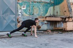 Stilig ung man, löpare i startposition från sida med dörren och grov vägg Kondition genomkörare, sport, livsstilbegrepp royaltyfri bild